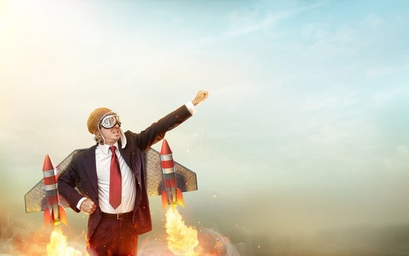 A businessman wearing a suit and strapped to metal wings with rockets prepares to lift off into the sky.
