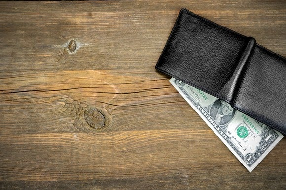 Wallet on a table with a dollar bill coming out.