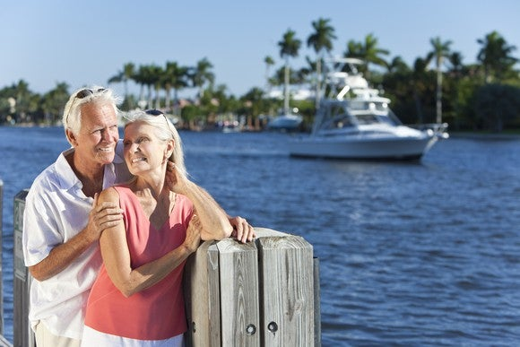 Older couple in front of water with boat in background