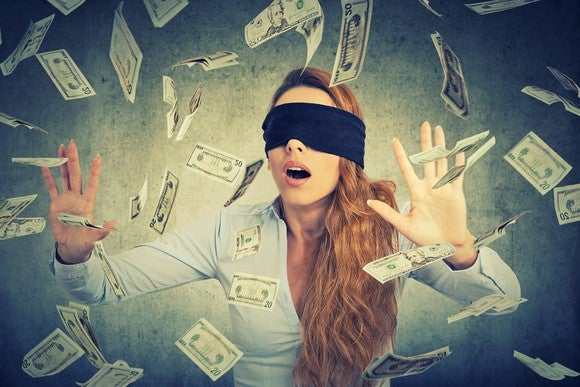 A blindfolded woman tries to catch paper money floating around her.