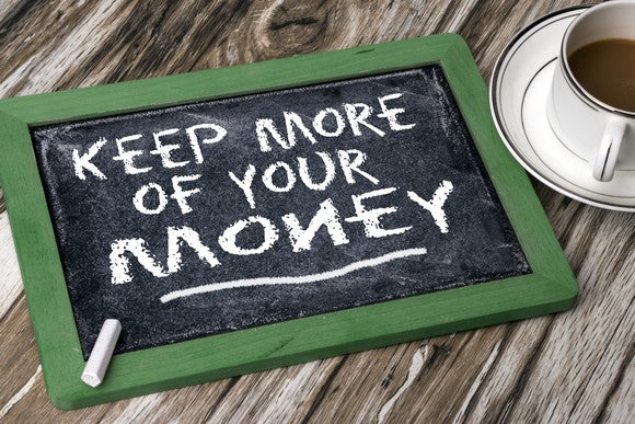 Miniature chalkboard on a wooden surface, next to a cup of coffee, with keep more of your money written on it