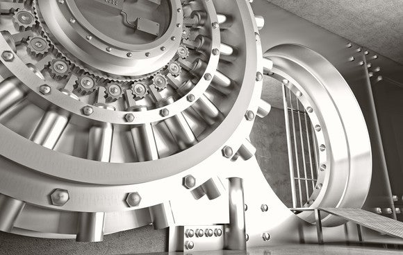 Bank vault with shiny silver round door and small view of inside of vault.
