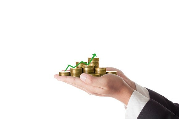 A businessman holding out his hands with coins and a green chart heading higher.