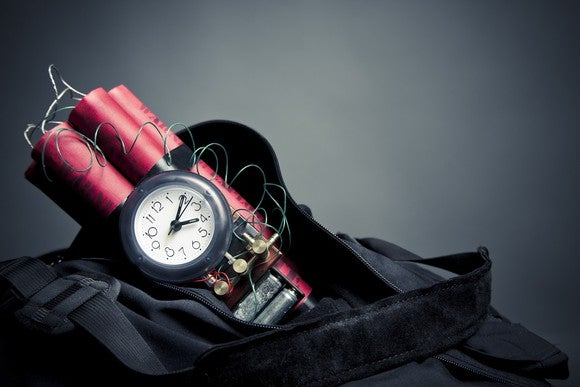 Black backpack holding sticks of red dynamite with a small clock attached to it.