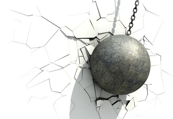 A metallic ball wrecking a white wall