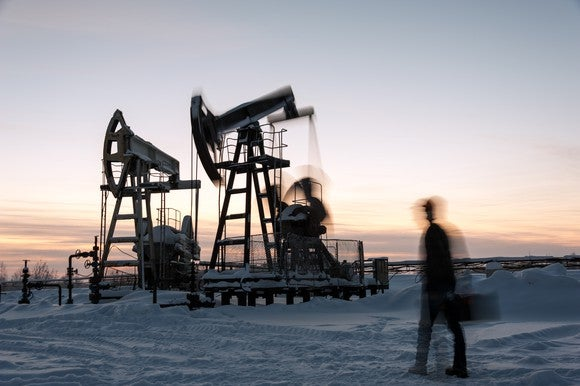 Long exposure shot of rig worker at a pumpjack in winter