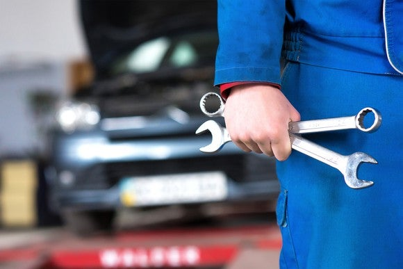 Worker holding two wrenches with a car in the background.