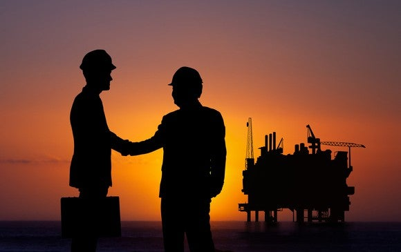 Silhouettes of two men shaking hands with an oil rig in the background.
