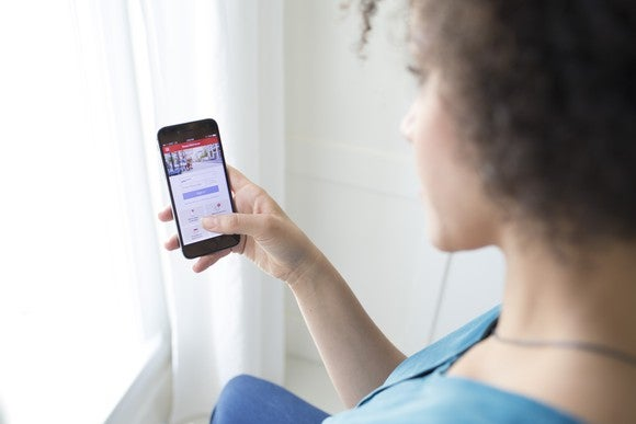 A woman using Bank of America's mobile app on a smartphone.