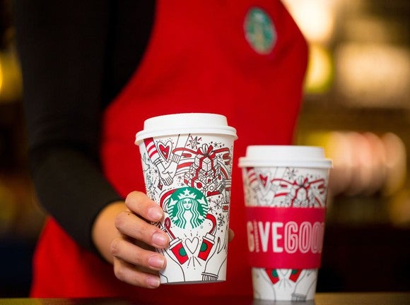 Barista with two Starbucks holiday cups