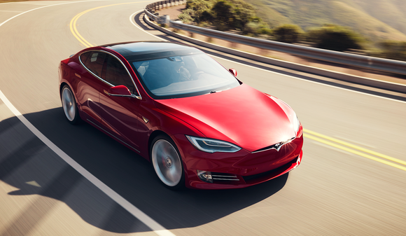 Red Tesla Model S car on road.