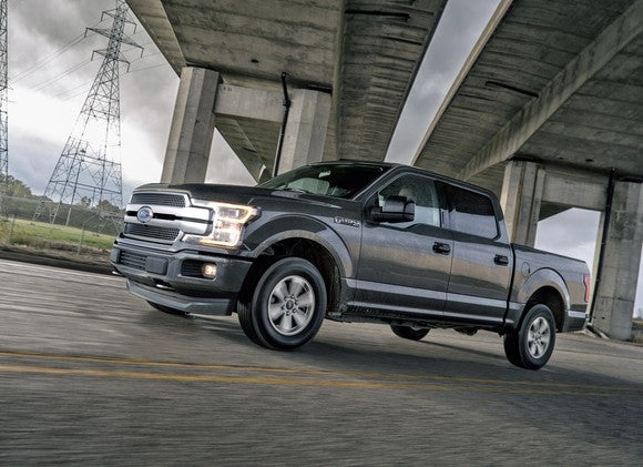 Ford's 2018 F-150 driving under a concrete bridge, with power lines in the background