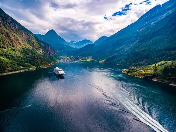 Cruise ship in Norwegian fjord, surrounded by mountains.