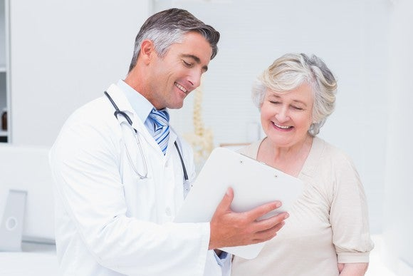 Doctor and patient looking at a piece of paper and smiling