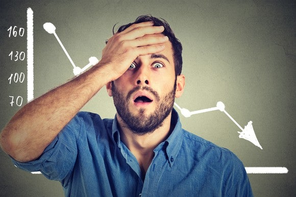 A shocked man standing in front of a downward trending graph.