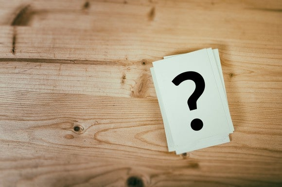 A question mark drawn on a note card that is sitting on a wooden table.