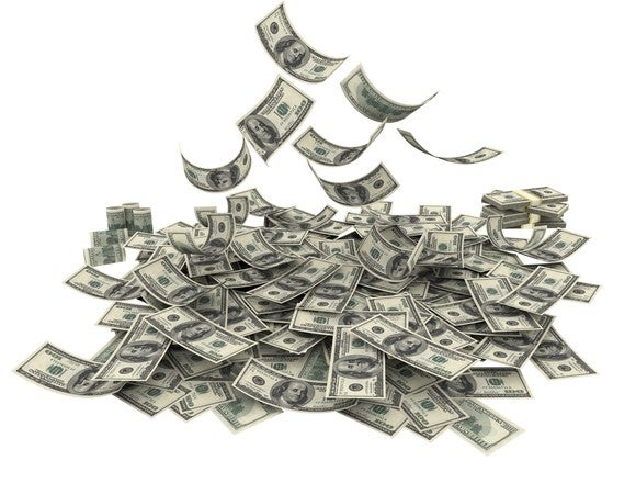 Money falling from above, forming a pile