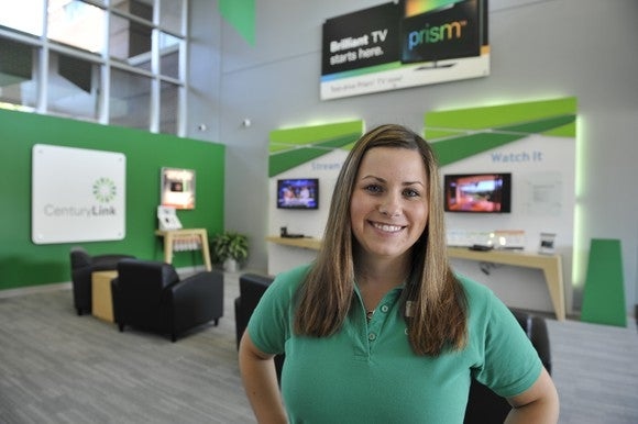 A woman in a green shirt in front of a CenturyLink and Prism TV display.