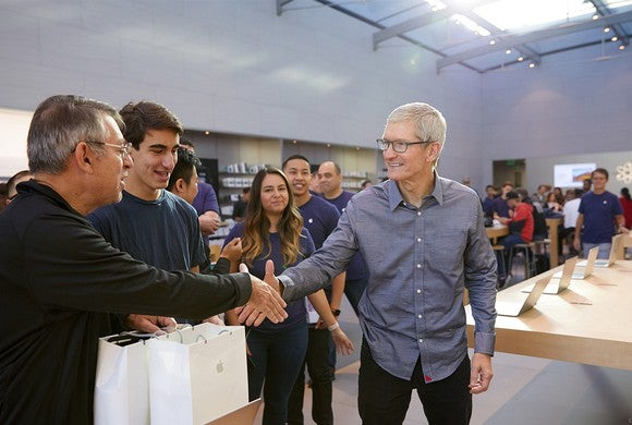 Apple CEO Tim Cook shakes hands with fans at an Apple store.
