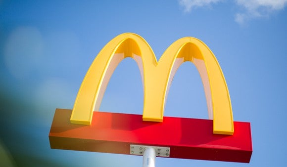 McDonald's Golden Arches signage against a blue sky.