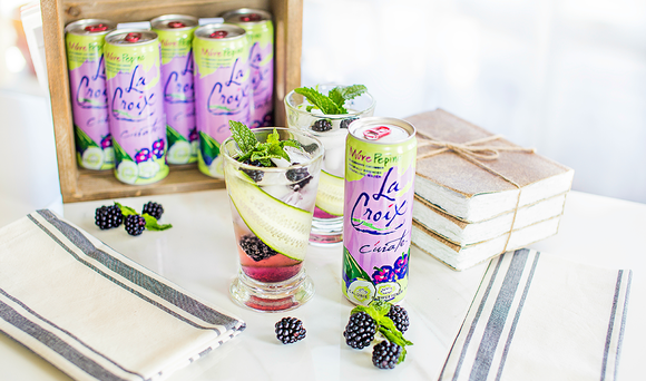 Display of La Croix Pepino flavor cans along with a glass with fruit in it.