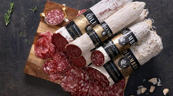 Rolls of salami piled high, with pieces freshly cut from the end.