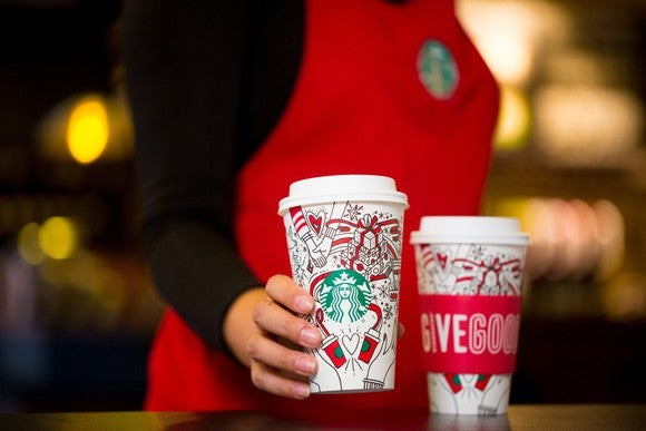 A barista holding Starbucks' 2017 Holiday cup