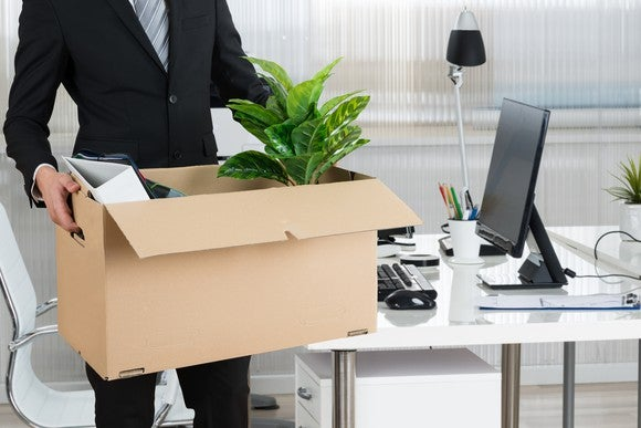 A professional man carrying a cardboard box filled with a plant and office supplies while walking away from a desk