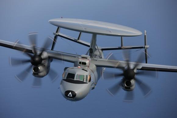 E-2 Hawkeye aircraft, airborne against a blue sky.