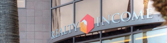 Awning with Realty Income logo on commercial building.