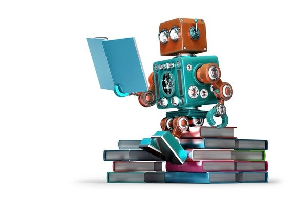 Toy robot sitting on pile of books reading.