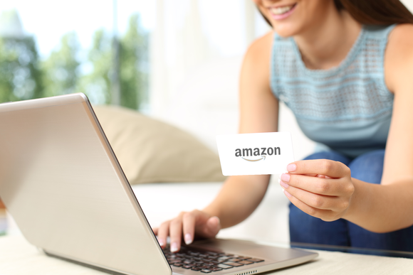 Smiling woman using a laptop while holding a credit card that features Amazon's corporate logo.