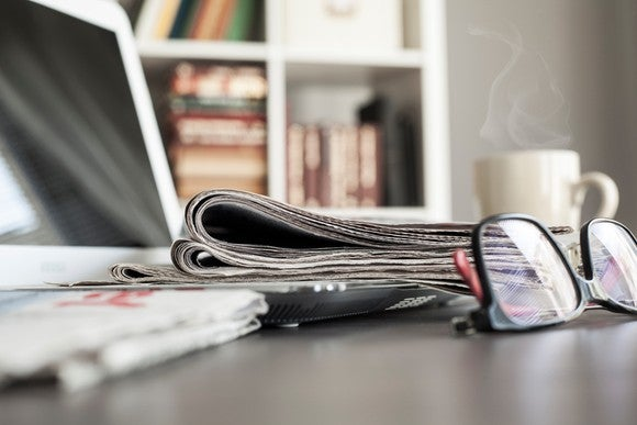 Close-up of a laptop, steaming cup of coffee, pair of glasses, and newspaper on desk.