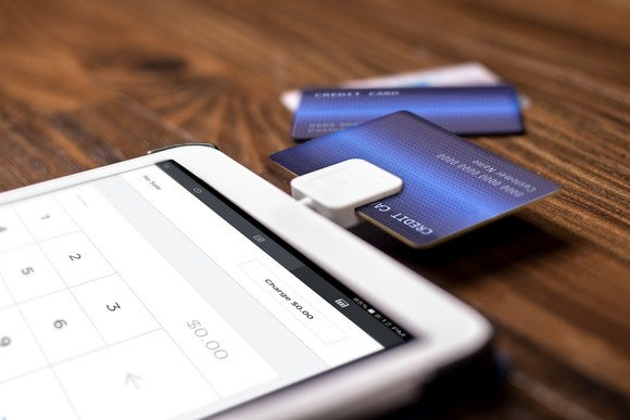 A Square card reader processing a credit card transaction on a tablet computer