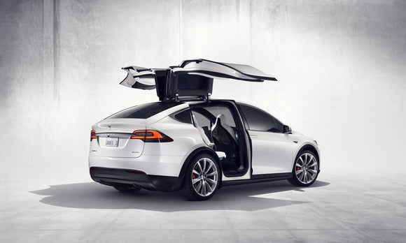 A white Tesla Model X with its gull-wing doors open