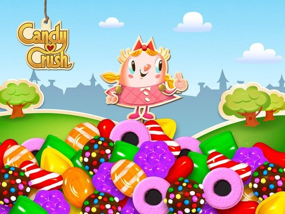A girl character from Candy Crush standing on top of a mountain of sweets.