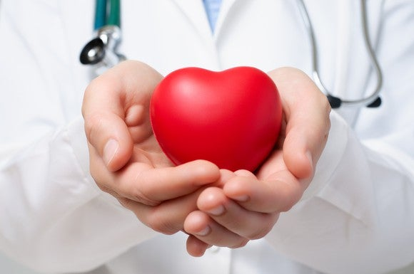 closeup on a doctor's hands holding a red plastic heart.