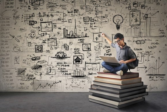 A person sitting on a stack of books using a computer and pointing at a wall behind him that's covered with drawings and ideas.
