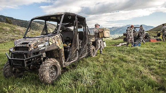 Hunters unloading a Polaris Ranger XP 1000 in a grass field