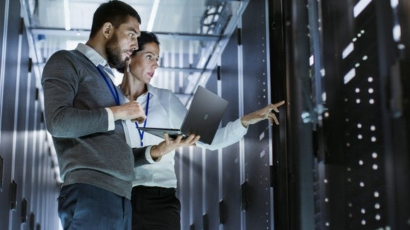 A man and woman stand inside a data center.