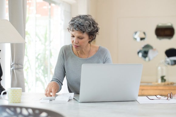 Older woman at a laptop with papers and receipts