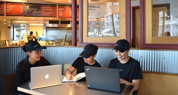 Chipotle employees sitting around a booth at a Chipotle using computers and writing in a notebook.