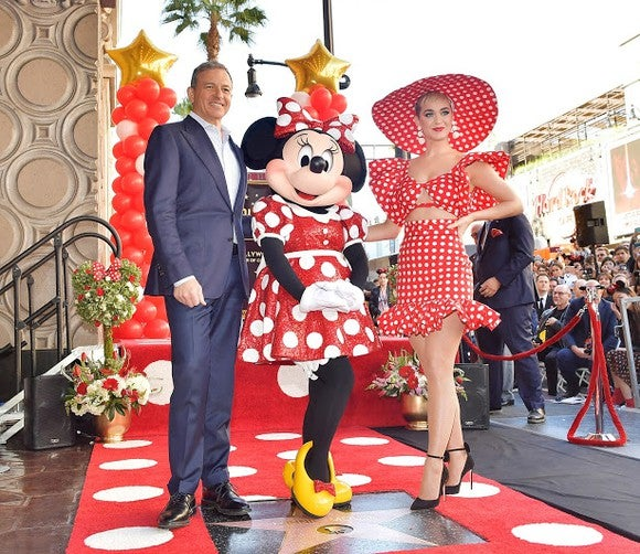 Minnie Mouse poses with CEO Bob Iger and a woman for Minnie's star on the Hollywood Walk of Fame