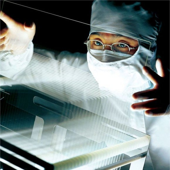 A Corning employee holds an LCD screen.