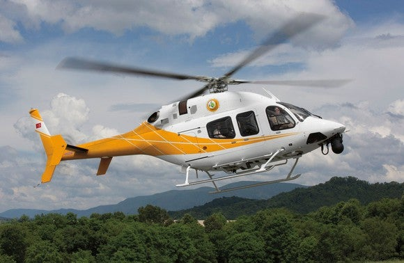 Yellow and white Textron Bell 429 Helicopter flying with mountains in the background