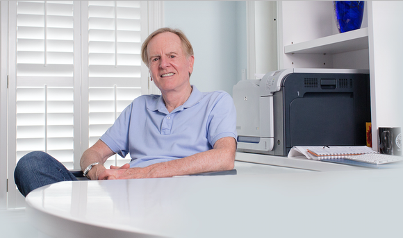 John Sculley sitting at a desk