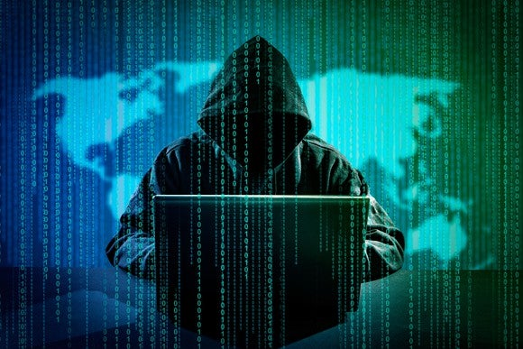 Hooded person sitting in front of computer with image of the world behind them.