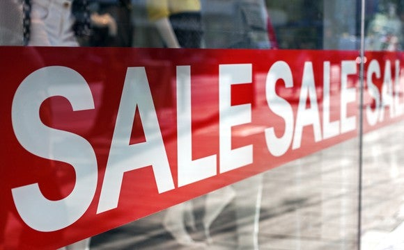 Sale sign in a storefront window.