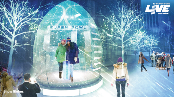 Two fans pose in a mock-up of a snow globe in downtown Minneapolis