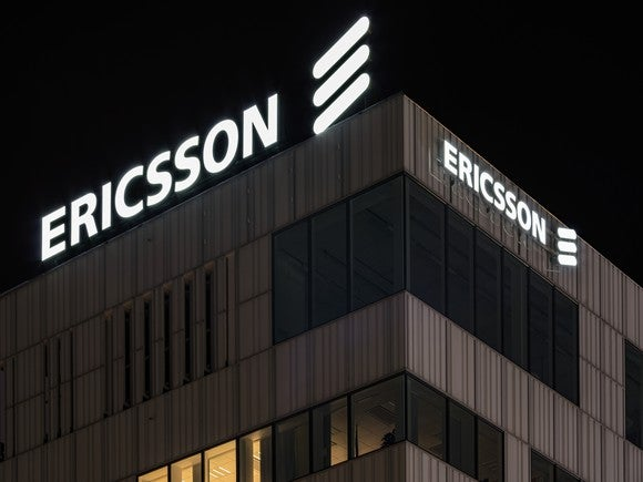 LM Ericsson's corporate logo atop the Stockholm HQ building, bright white against a black sky.